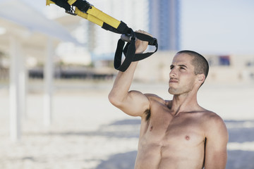 Young male athlete working out at the beach
