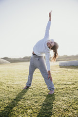Young woman doing stretches on the grass
