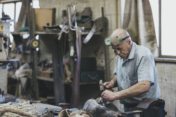 Old man working with hammer and chisel on bronze sculpture