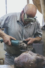 Old craftsman sanding a bronze sculpture