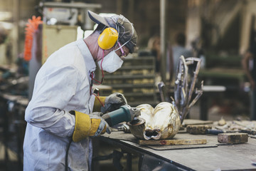A craftsman with protective gear polishing a bronze sculpture