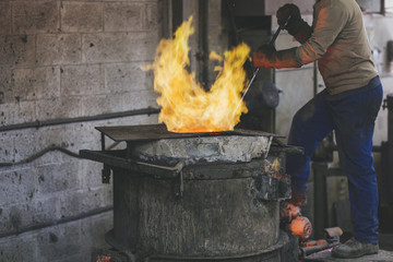 Closeup of craftsman stirring melted bronze in a foundry