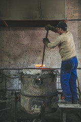 Craftsman checking melted bronze in a foundry