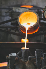 crucible pouring melted bronze into lost wax casting mold