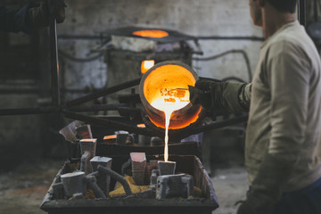 Man pouring melted bronze into molds using a crucible
