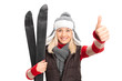 Woman holding skis and giving thumb up