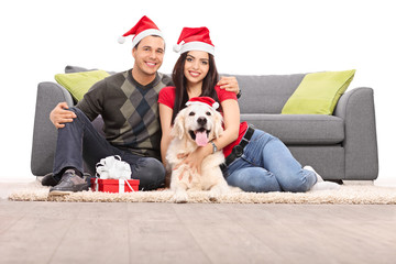 Young couple with Santa hats sitting with a dog