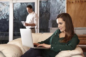Paar zuhause, Frau am Latop, Mann mit Tablet
