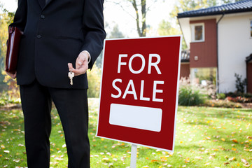 Estate agent with keys and sign