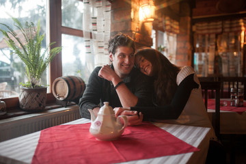 Couple sitting in a restaurant hugging and smile