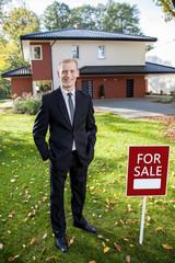 Estate broker standing outside the house