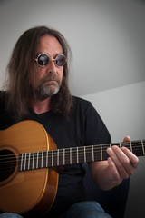 Middle-aged man playing guitar.