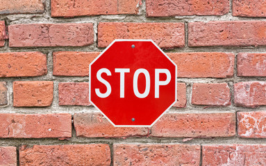 Bright stop sign attached to large brick siding