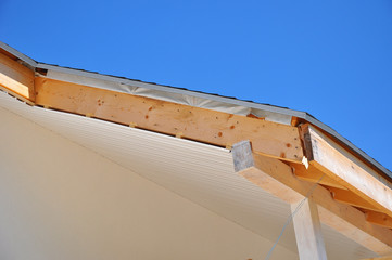Corner of house with eaves. Install soffits against blue sky