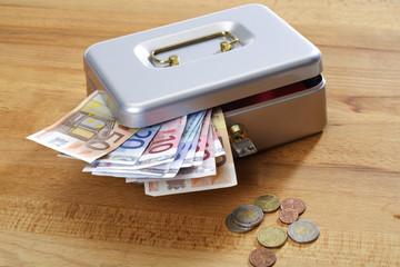 Geldkassette mit Euroscheinen und Euromünzen auf Holzuntergrund