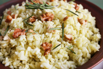 Rice with walnuts and rosemary in plate, macro
