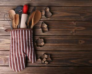 Set of kitchen utensils in mitten on wooden planks background
