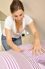 Frau bezieht Betten mit Bettwäsche