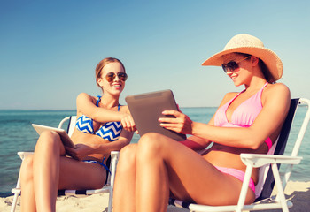 smiling women with tablets pc computers on beach