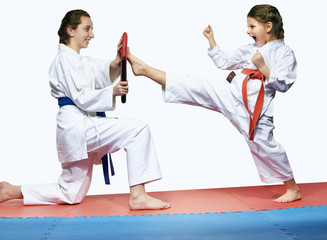 Older sister helps younger one to train a kick