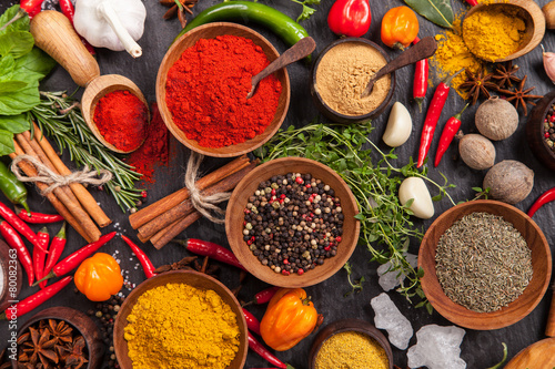 Fototapeta Various spices on black stone