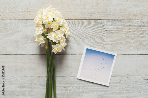 Papiers peints Narcisse Bunch of white narcissus and printed photos on a wooden table