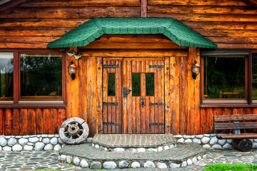Wooden brown cottage in the countryside with a wheel on porch
