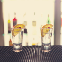 Two tequila shots with lemon