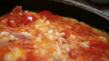 omelet with vegetables and ham fried in a pan. Close up. Macro