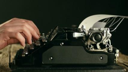 Hands writing on old typewriter
