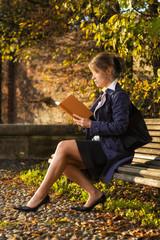 Ragazza che legge un libro in un parco