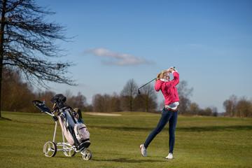 Junge schlanke Frau spielt einen Annäherungsschlag beim Golf