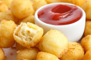 Bowl of fried small potato balls on white. Pot of ketchup.
