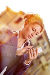Ragazza che utilizza lo smartphone in città