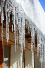 Transparent icicles hanging from a mountain hut roof in a sunny