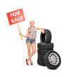 Woman holding a for sale sign by a pile of tires