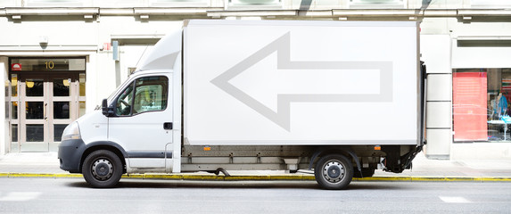 White truck in profile, with arrow