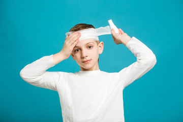 Boy taping up bandage on his head