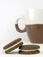 Chocolate biscuits with a milk cream filling and coffee cup
