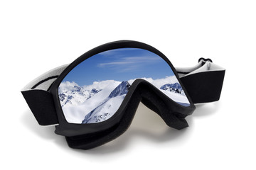 Ski goggles with reflection of mountains at sun day