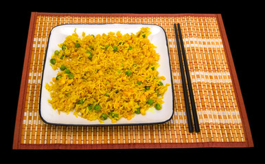 Rice with vegetables and chopsticks on bamboo mat