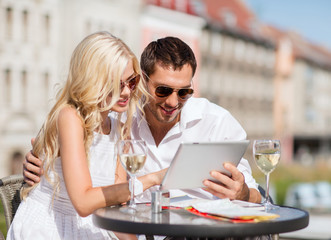 couple looking at tablet pc in cafe