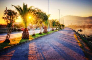 Promenade along the river bank at warm sunset. HDR image
