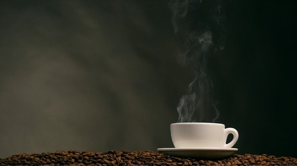 Cup of coffee on dark background. Slow motion