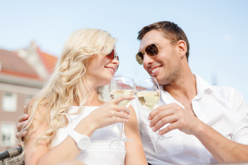 smiling couple in sunglasses drinking wine in cafe