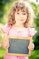 Child holding blackboard blank