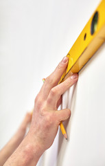 close up of male hands with level measuring wall