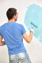 man with roller painting wall in blue at home