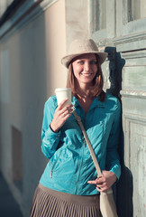 Beautiful hipster woman in hat and blue jacket with cup of coffe