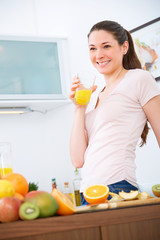 Young beauty with orange Juice in the kitchen